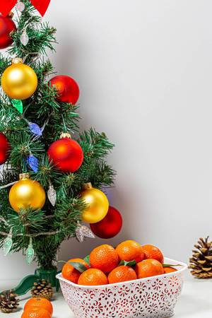 Decorated Christmas tree with a box of ripe tangerines (Flip 2019)