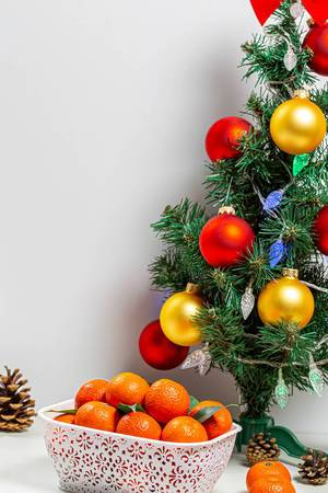 Decorated Christmas tree with a box of ripe tangerines