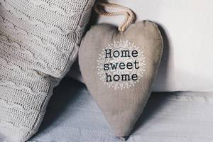 Decorative Pillow in Heart Shape with Writing Home sweet home on a Sofa