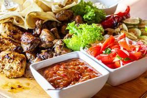 Deftiger Fleischteller: Gegrilltes Fleisch und Gemüse mit scharfer Soße und frischem Gemüse