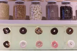 """Dekoration mit Donut-Girlanden und gefüllten Einmachgläsern mit Nüssen und Schokolade, im Feinkostladen """"chök"""" in Barcelona, Spanien"""