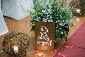 Dekoration mit weißem Blumenstrauß, Kerze in Strohkugel und Holztafel mit Zitat auf Boden