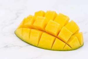 Dekorative Mango in Igelform angerichtet, auf einem weißen Marmortisch