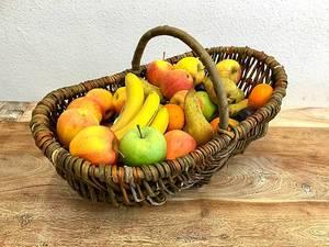 Dekorativer Flechtkorb mit saisonalem Obst im Herbst