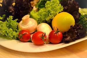 Dekorativer, kunstvoller Salatteller mit Pilzen und Tomaten