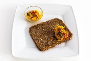 Deli Genuss - Süßkartoffelaufstrich präsentiert auf einem kernigen Vollkornbrot auf einem weißen Teller