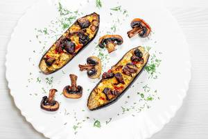Delicious baked eggplant with champignons on plate. Top view