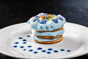 Delicious dessert with blue cream on a white plate