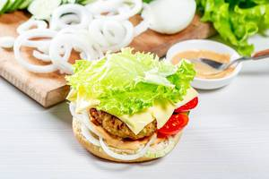 Delicious fresh homemade burger with lettuce, cheese, onion and tomato on a white wooden background