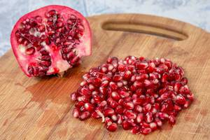 Delicious Fresh Pomegranate seeds on the wooden board (Flip 2019)