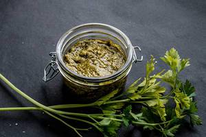 Delicious green pesto in a glass jar.