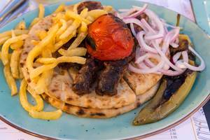 Delicious kebab pita with tomatoes from Paros, onions and grilled Greek paprika on blue plate