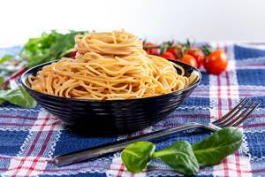 Delicious spaghetti in a black bowl with herbs and tomatoes in the background (Flip 2019)