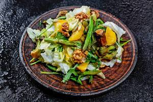 Delicious vegetarian salad with asparagus, broccoli, mushrooms, lettuce, arugula, orange, seeds and nuts