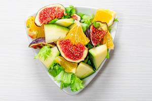 Delicious vegetarian salad with fresh vegetables and fruits in a triangular plate. Top view (Flip 2019)