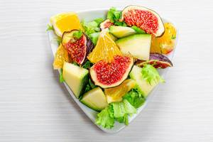 Delicious vegetarian salad with fresh vegetables and fruits in a triangular plate. Top view