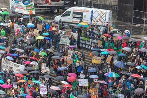 Demonstrating youngsters with colorful signs and umbrellas at the Fridays For Future demonstration for the environment