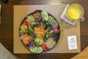 """Der bunte, spanische Salat """"Ensalada del Sol"""" neben einer Goldenen Milch im veganen Restaurant Petit Brot in Barcelona, Spanien"""