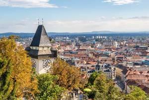 Der historische Uhrturm zwischen Bäumen in Graz, Österreich
