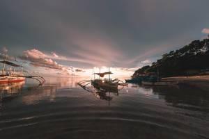 Der Sonneuntergang hinter einem Boot in Sipalay