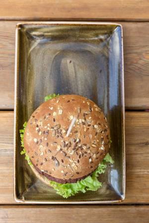 """Der vegan Vitamin B 12 Burger """"Naturbursche"""" mit Zwiebeln und Champions von Moving Mountains, auf einem Holztablett im """"Hans im Glück"""" Restaurant"""
