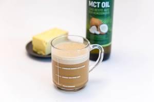 """Der Wachmacher mit Sättigungsgefühl """"Bullet Proof Kaffee"""" in einer Glastasse, vor einer Flasche MCT-Öl von Woldo Health und einem Stück Butter"""