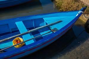 Detail-Aufnahme eines blauen Fischerbootes mit einem Fischerspeer, Paddel und ein paar leeren Dosen Bier