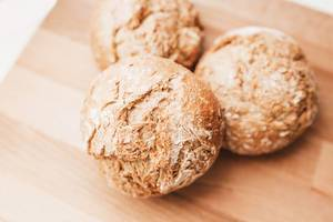 Detail of fresh baked wholemeal bread rolls on wooden board