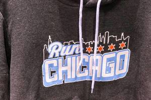 """Detail of grey hoodie with """"Run Chicago"""" graphic in white and light blue, skyline of the city and four red stars"""