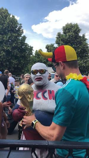 Deutscher und russischer Fußball-Fan halten zusammen den WM-Pokal