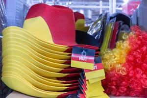 Deutschland Fanartikel - gestapelte Hüte, verpackte Fahnen und Perücken
