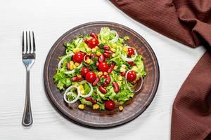 Diät-Salat mit buntem Gemüse und roten Bohnen auf einem braunen Teller, mit einer Gabel und Küchentuch, auf dem Tisch