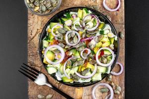 Diät Salat mit Gurken, Sonnenblumenkernen, Zwiebeln und Avocado auf einem Holzschneidebrett von oben fotografiert