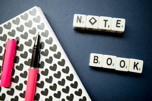 Dice reading NOTE BOOK, small note book, and pen