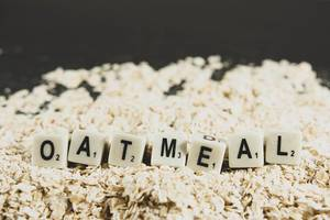 Dice reading OATMEAL over oats