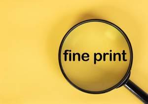 """Die Aufschrift """"fine print"""" - Kleingedruckte - in schwarz auf gelbem Hintergrund, vergrößert unter einer Lupe dargestellt"""