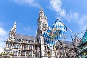 Die bayrische Landesflagge mit Regenbogenfahnen am Marienplatz im Hintergrund,  für mehr Toleranz gegenüber der LGBTQ-Community