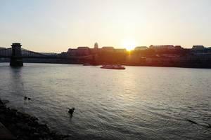 Die Donau in Budapest, Ungarn, mit Sonnenuntergang hinter den Häusern der Stadt
