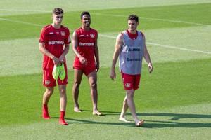 Die drei Fußballer Lucas Alario, Wendell und Kai Havertz gehen nach dem Fußballtraining glücklich und barfuß vom Spielfeld