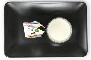 Die faire Milch - Gentechnikfreie - Deutsche Vollmilch im Glas und Verpackung auf schwarzem Teller - Aufsicht