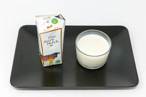 Die faire Milch - Gentechnikfreie - Deutsche Vollmilch im Glas und Verpackung auf schwarzem Teller