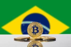 Die Flagge Brasiliens mit einem Set aus vier goldenen Bitcoins im Vordergrund