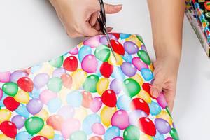 Die Hände einer Frau beim bunten Geschenkpapier schneiden mit einer Schere