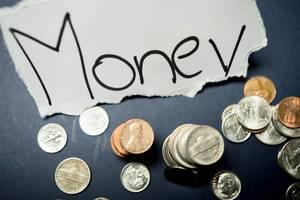 Die Inschrift Money mit Münzen auf schwarzem Hintergrund