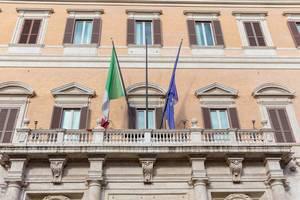 Die Italienische und die Europäische Fahne an einem Gebäude auf einem Platz in Rom