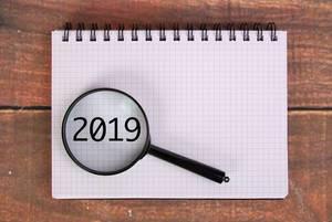 Die Jahreszahl 2019 auf einem Karoblock, vergrößert dargestellt unter einer Lupe