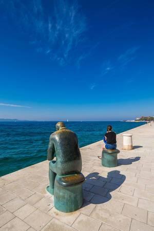 Die Kupferstatue des Spiri Brusini mit einer Muschel und eine Frau an der Promenade in Zadar