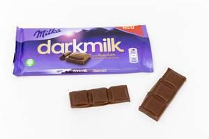 """Die neue Milka - Schokolade """"darkmilk"""" aus Aplenmilch mit lila Verpackung auf weißem Untergrund"""