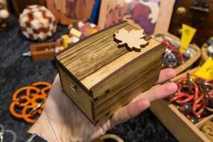 Die Rätsel Manufaktur ein Mann hält eine Holztruhe in der Hand im Hintergrund viele knifflige Handrätsel