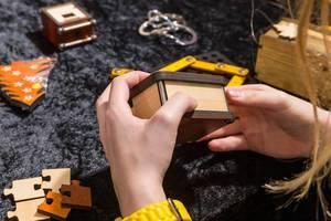 Die Rätsel Manufaktur eine Frau hält eine Holzbox in den Händen umgeben von verschiedenen Rätseln
